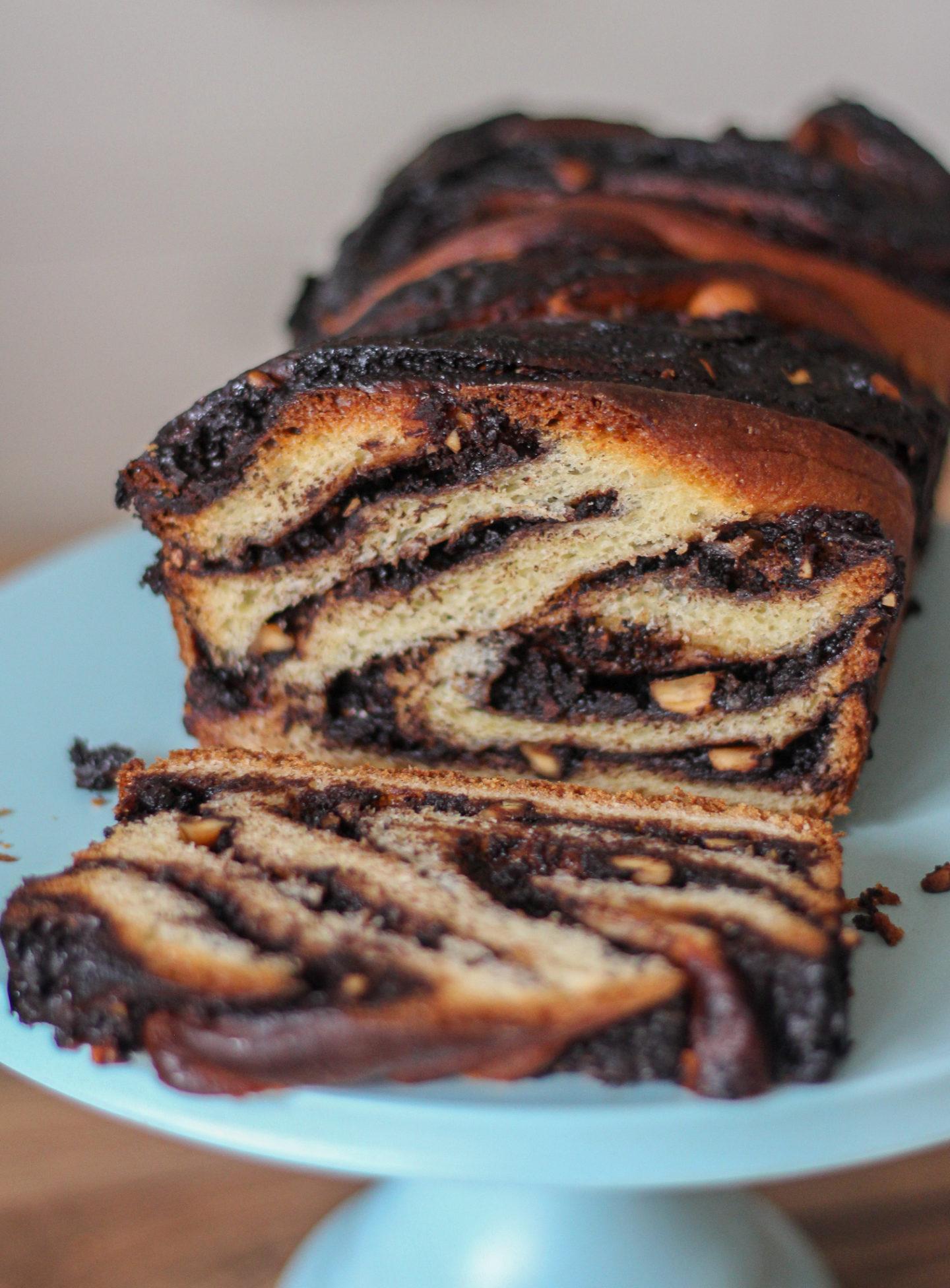 view inside a sliced chocolate and hazelnut babka on a cake stand