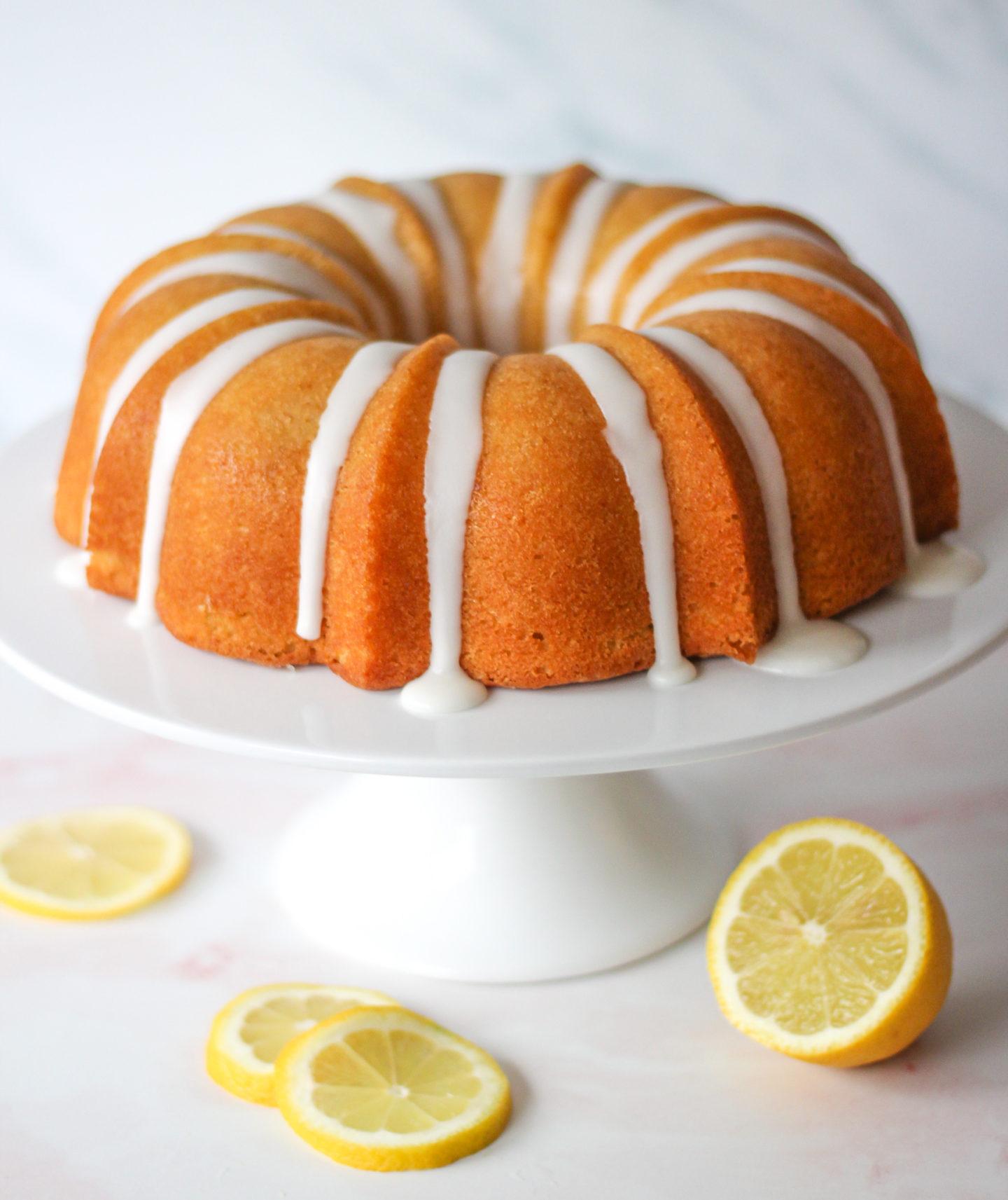 Whole unsliced lemon drizzle bundt cake on a cake stand