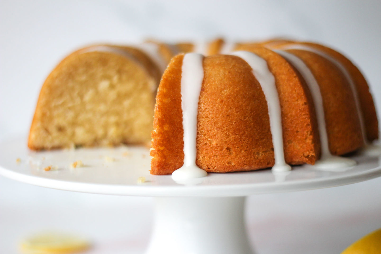 Sliced lemon drizzle bundt cake on cake stand
