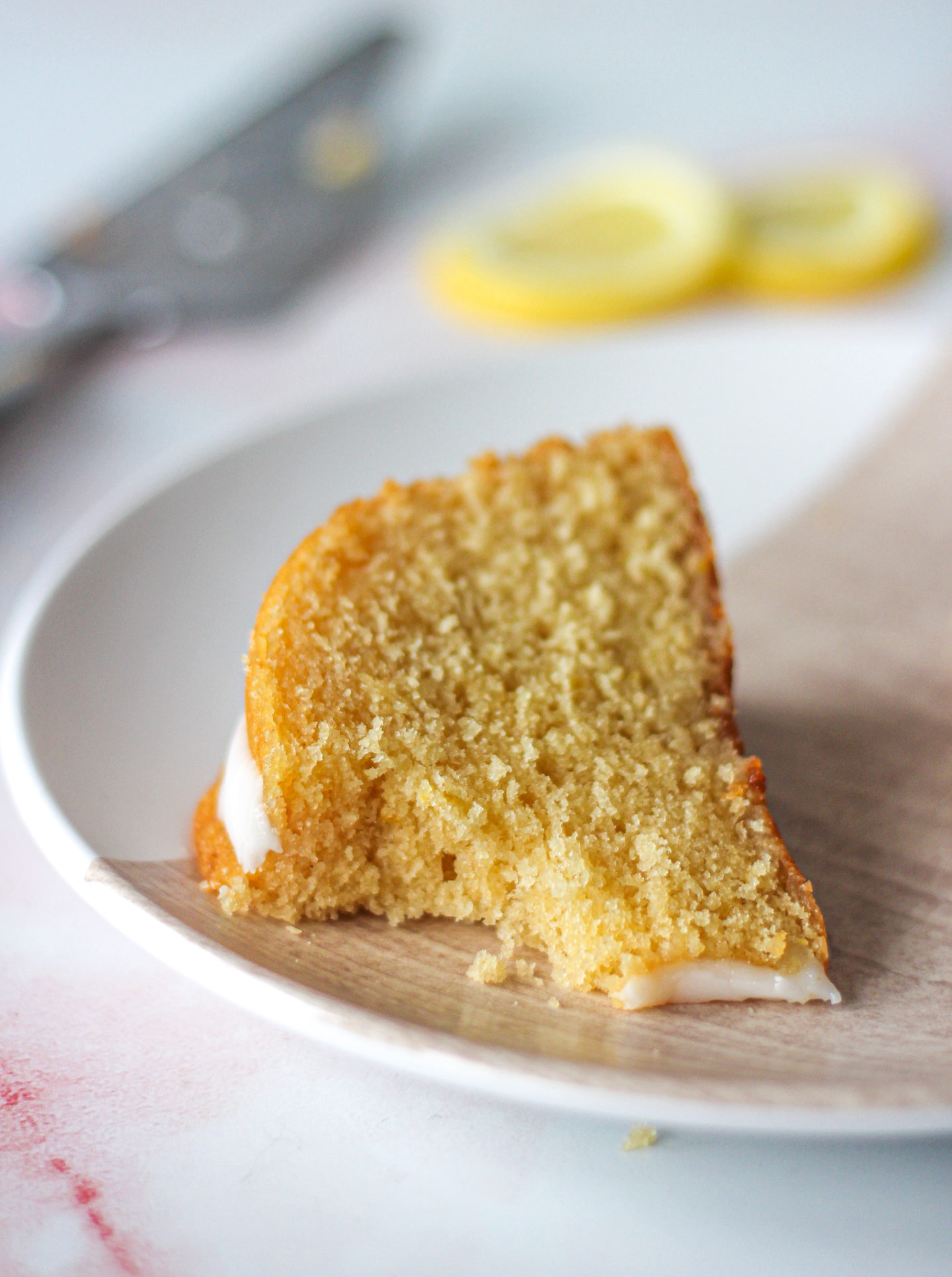 Close up of a slice of lemon drizzle bundt cake on a serving plate